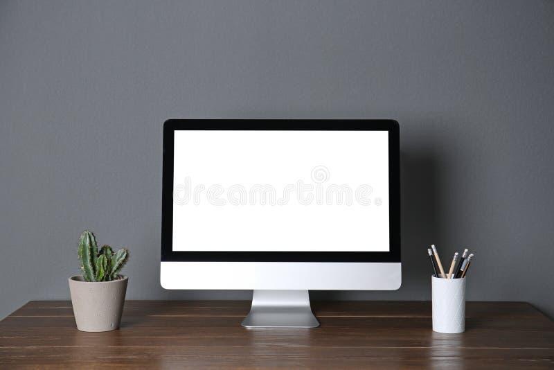 Monitor de computadora moderno en la pared del gris de la tabla fotografía de archivo