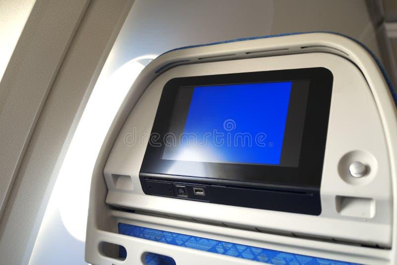 Monitor do avião atrás do assento do passageiro com luz do sol completamente do monitor da janela e da tela vazia fotografia de stock royalty free