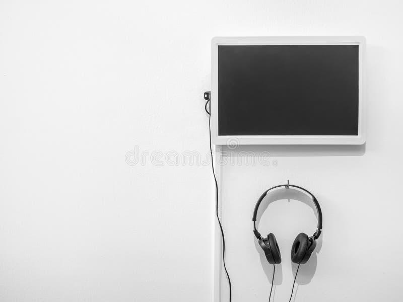 Monitor e fones de ouvido vazios na parede branca imagens de stock