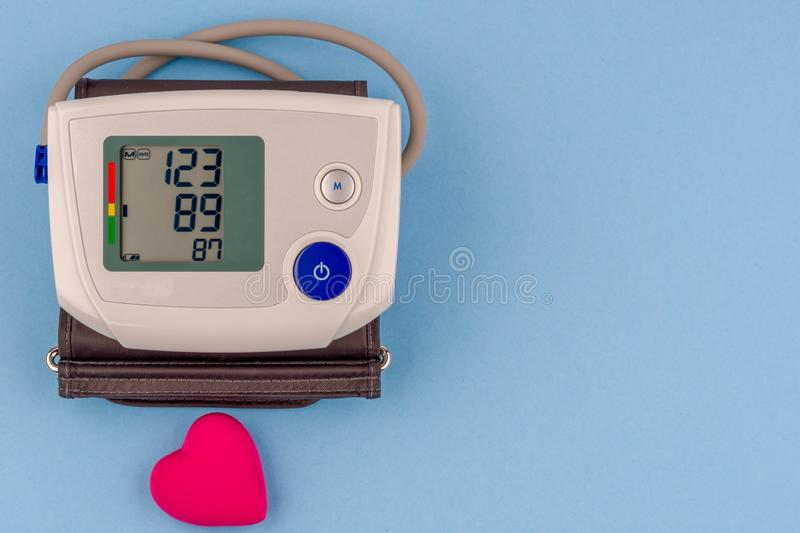 Monitor eletrônico moderno da pressão sanguínea com coração vermelho em um fundo azul imagens de stock royalty free