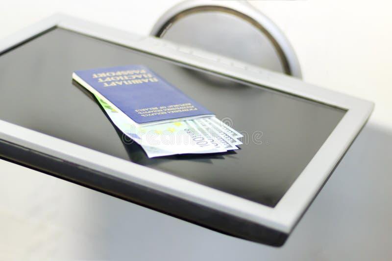 monitor em um fundo branco mas não isolado Passaporte do teclado e dólares e euro azuis do dinheiro imagem de stock