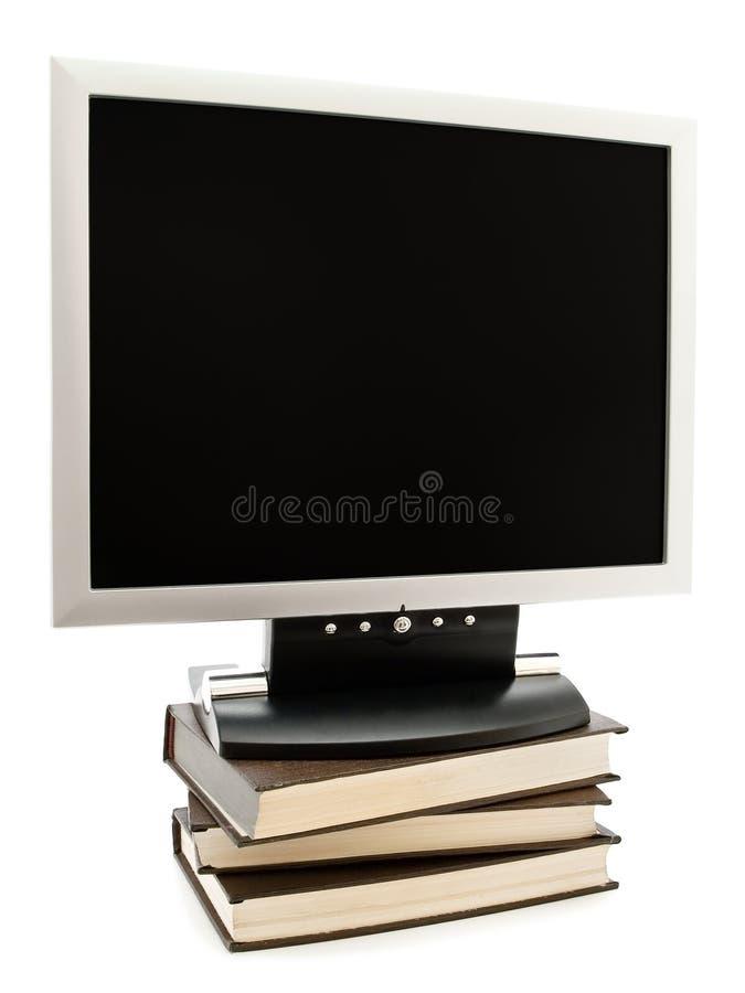 Monitor nos livros fotografia de stock