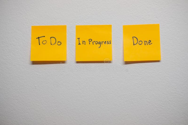 Monitor task of work concept, To do, In progress, Done Note reminder yellow sticker or post note on a white wall close up,. stock image
