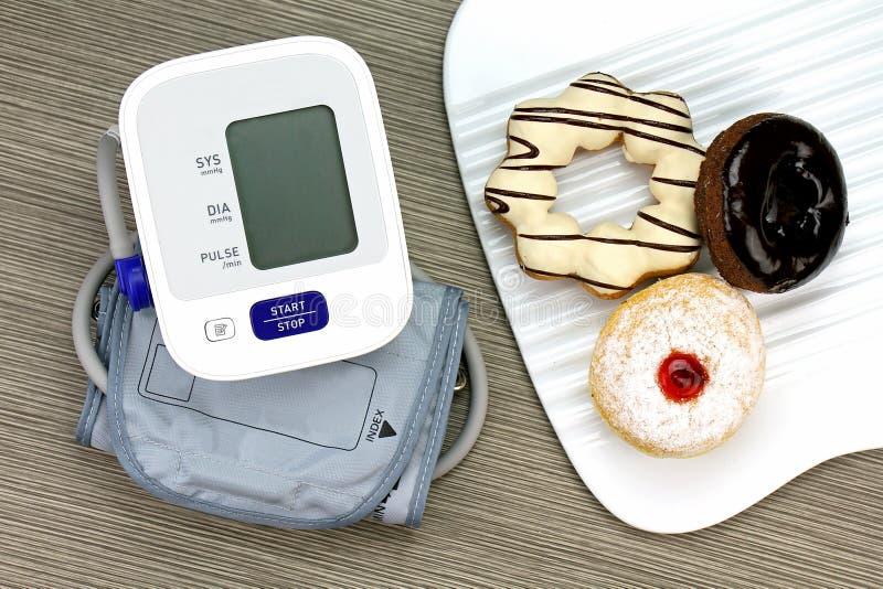 Monitor y buñuelo, comida malsana de la presión arterial de Digitaces fotografía de archivo