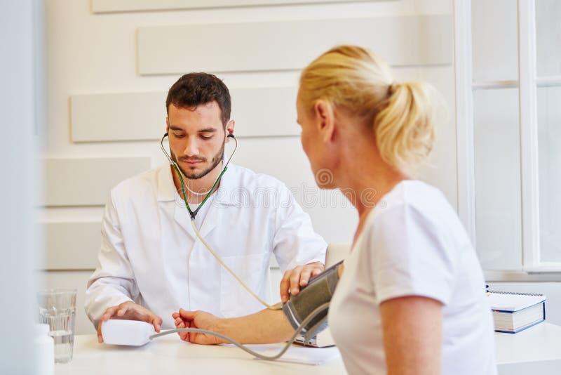 Monitoraggio di pressione sanguigna all'ufficio di medico immagini stock libere da diritti