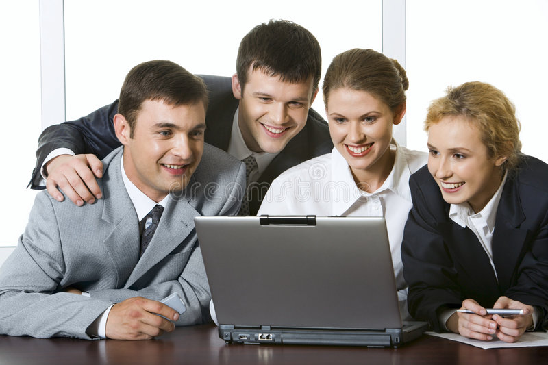 Monitoring. Group of four young businesspeople gathered together around the laptop discussing interesting question