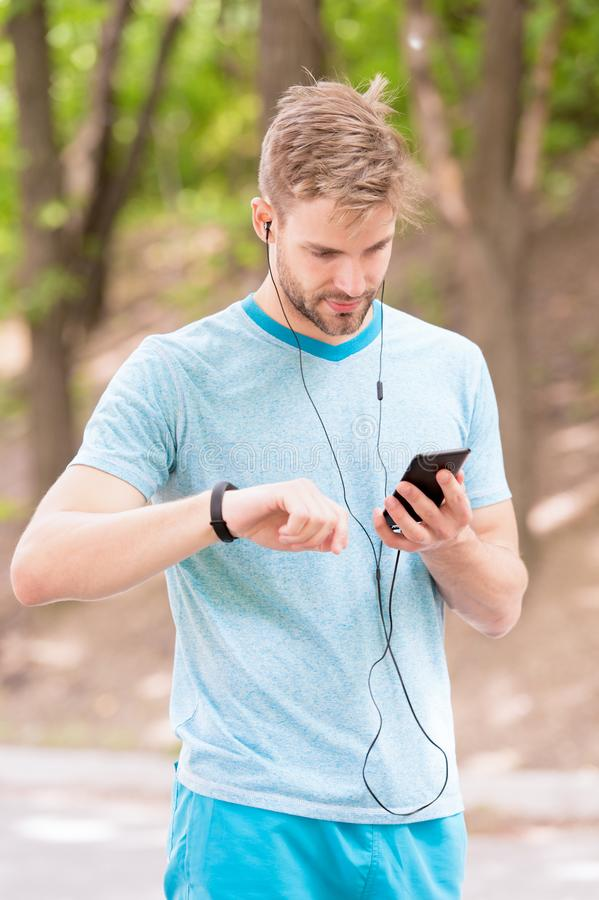 Monitoring and boosting his training. Sportsman tracking his training with fitbit and smartphone. Fit man paring royalty free stock images