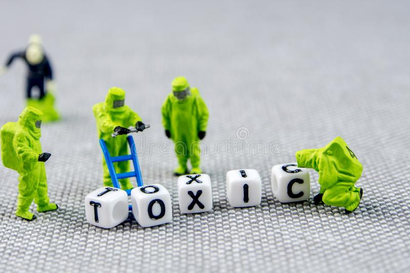 Monitoring and solving the problem with toxic word, substituting it with positive life posture. Closeup of miniature figurines dressed like members of firemen royalty free stock photos