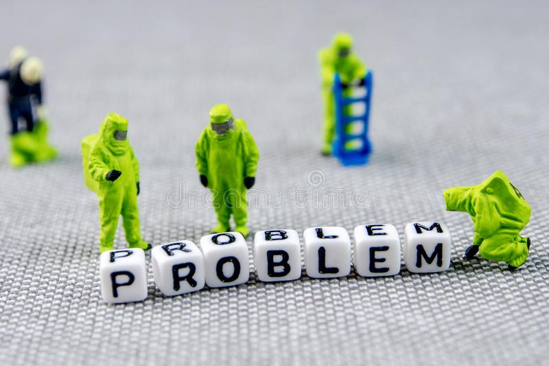 Monitoring and solving the problem with toxic word, substituting it with positive life posture. Closeup of miniature figurines dressed like members of firemen royalty free stock photo