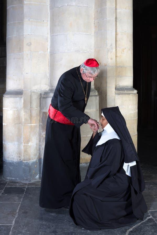 Monja que besa al cardenal del anillo fotografía de archivo
