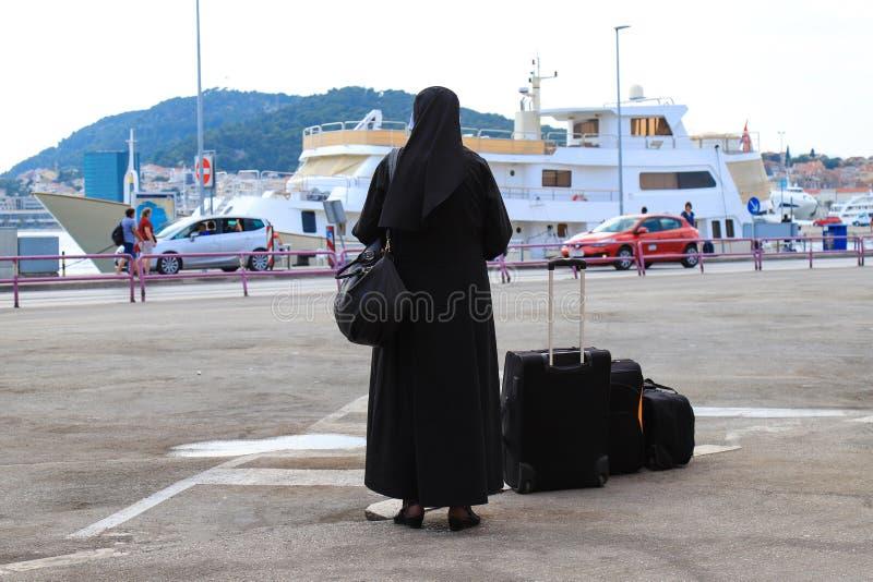 Monja que viaja con las maletas y el equipaje Una mujer en ropa monástica negra está esperando un autobús en la costa del viejo fotografía de archivo