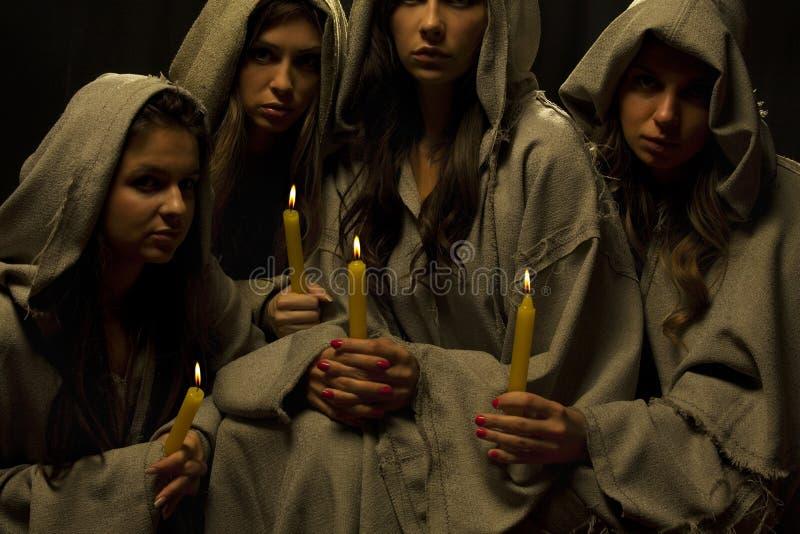 Monjas praing con las velas foto de archivo