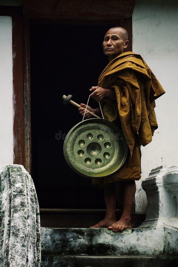 monje budista con un gongo delante de la entrada de su monasterio imágenes de archivo libres de regalías