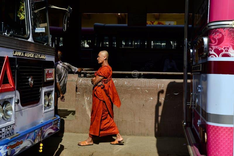 Monje budista en trajes anaranjados en un término de autobuses fotos de archivo