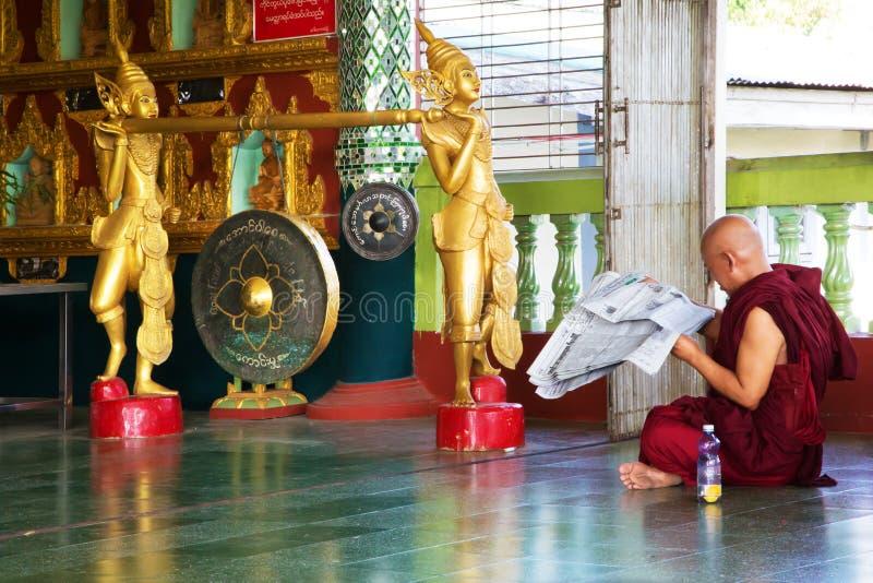 Monje budista que lee el periódico foto de archivo
