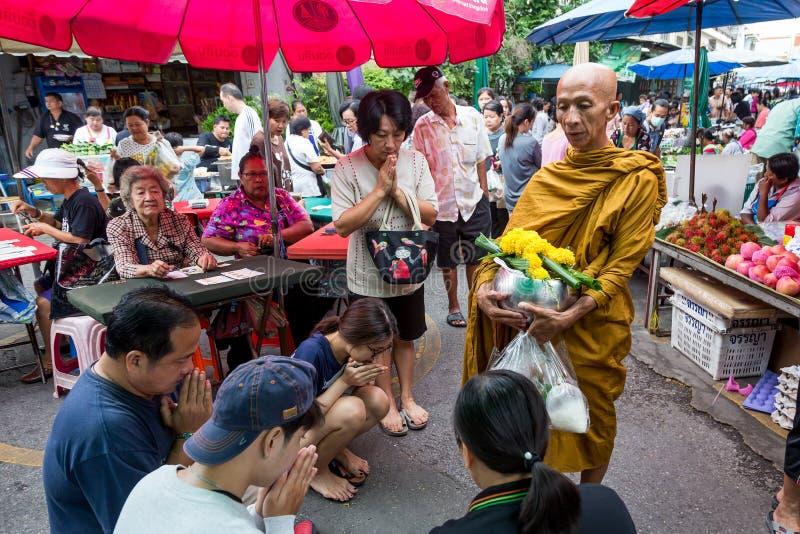 Monje tailandés que canta para la gente local en un mercado fresco en Phisanu imagen de archivo libre de regalías