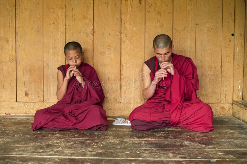 Monjes budistas butaneses del novato que sientan y que tocan la flauta, Bhután imagenes de archivo