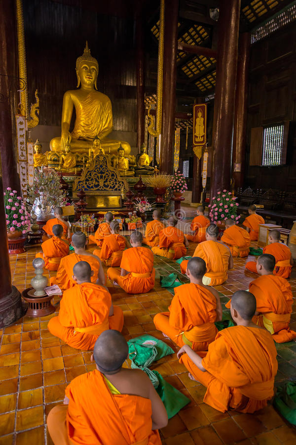 Monjes budistas jovenes que ruegan delante de la imagen de Buda foto de archivo