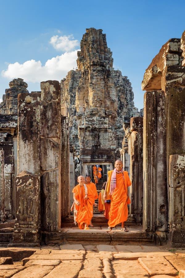 Monjes budistas jovenes que salen del templo de Bayon en Angkor Thom foto de archivo libre de regalías