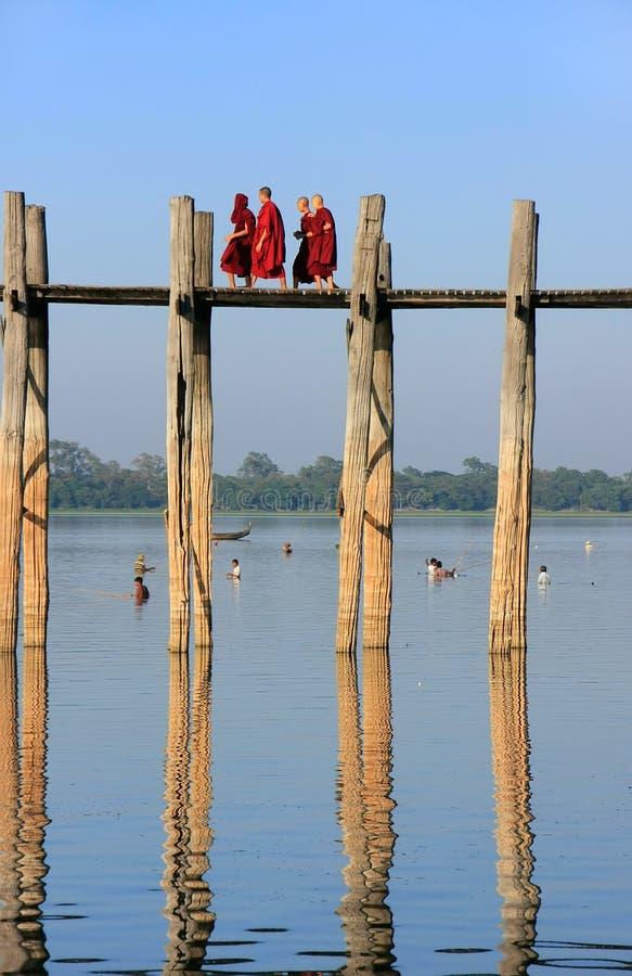 Monjes budistas que caminan en el puente de U Bein, Amarapura, Myanmar fotos de archivo