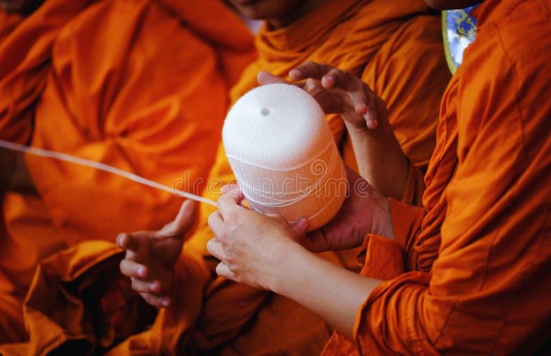 Monjes budistas tailandeses que ruegan en templo en el templo budista que sostiene el cordón sagrado o la prensa santa del hilo l imagen de archivo