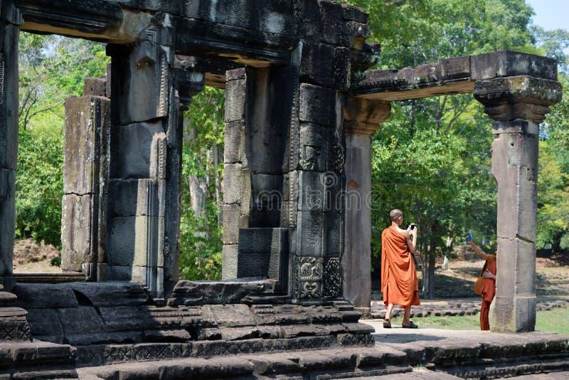 Monjes camboyanos jovenes en Angkor Wat que juega con sus teléfonos imágenes de archivo libres de regalías