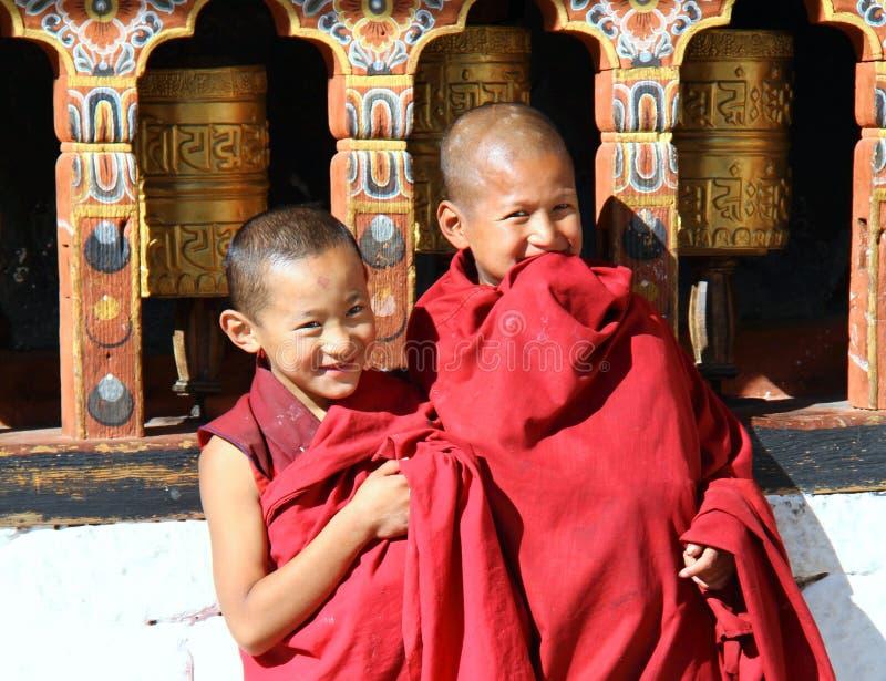 Monjes jovenes sonrientes que hacen una pausa las ruedas de rezo religiosas en el dzong de Paro Rinpung, Paro, Bhután fotos de archivo libres de regalías