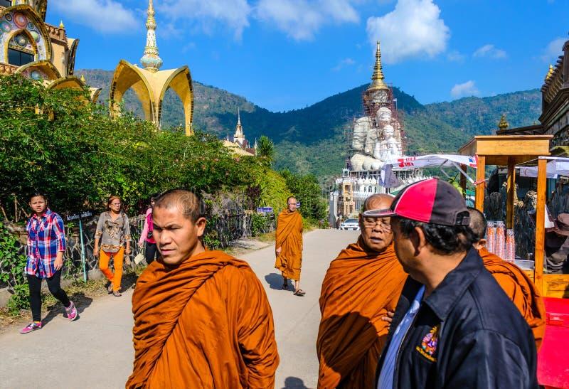 Monjes que caminan en la calle debajo del cielo azul en Phetchabun imagenes de archivo