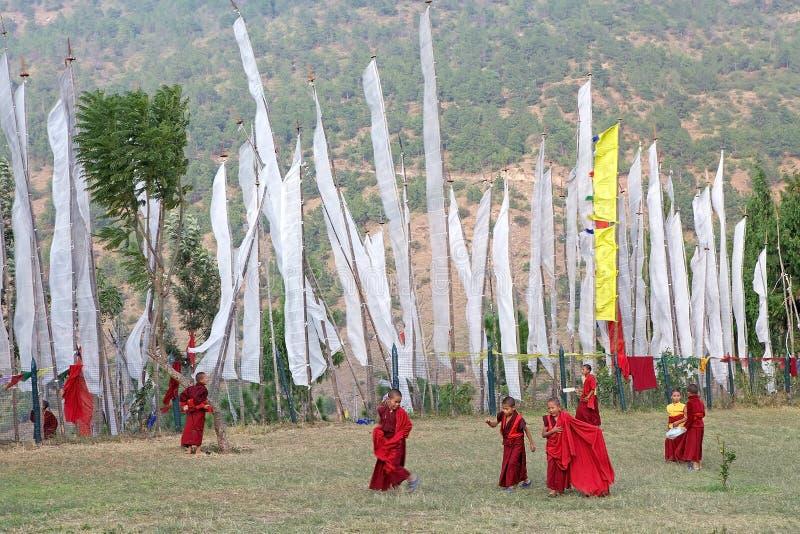 Monjes y banderas del rezo, Chimi Lhakang, Punakha, Bhután imágenes de archivo libres de regalías