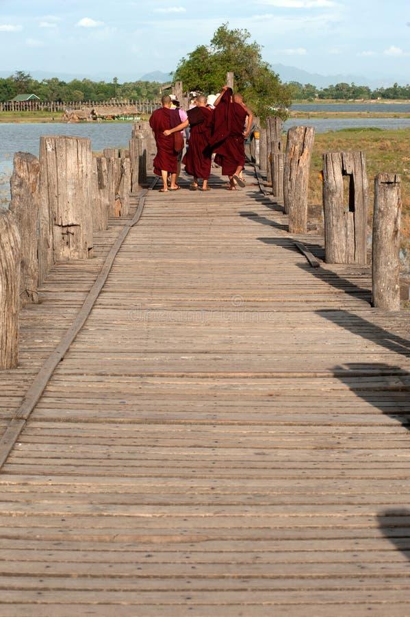 Monjes y visitantes que caminan en el ฺBridge de U-bein, Myanmar foto de archivo libre de regalías