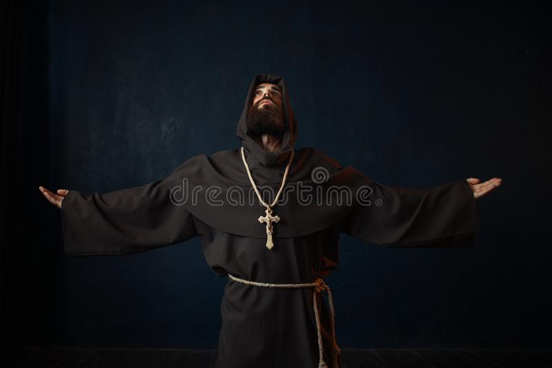 Monk in black robe with hood kneeling and praying. Religion. Mysterious friar in dark cape royalty free stock images
