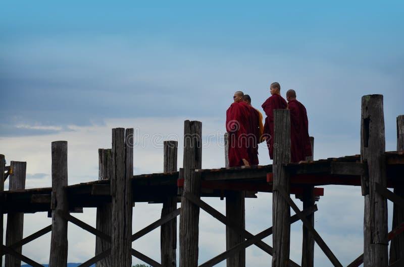 Monk of Burma walking cross over lake at U Bein Bridge stock photos