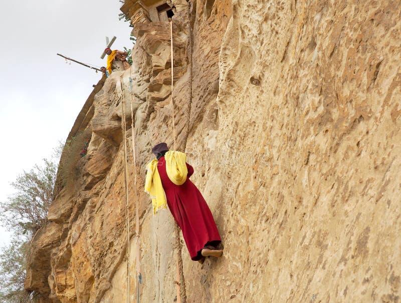 Monk climbing a rock wall at Debre Damo Monastery, Ethiopia stock images