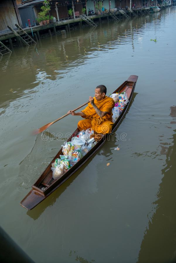 Monk Collecting Alms at Amphawa River stock photo