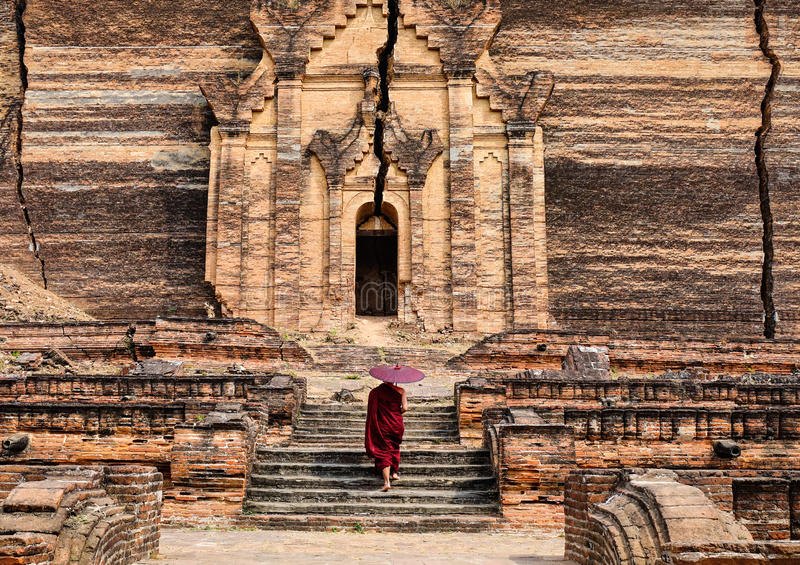 A monk coming to ancient pagoda in Mandalay, Myanmar stock image