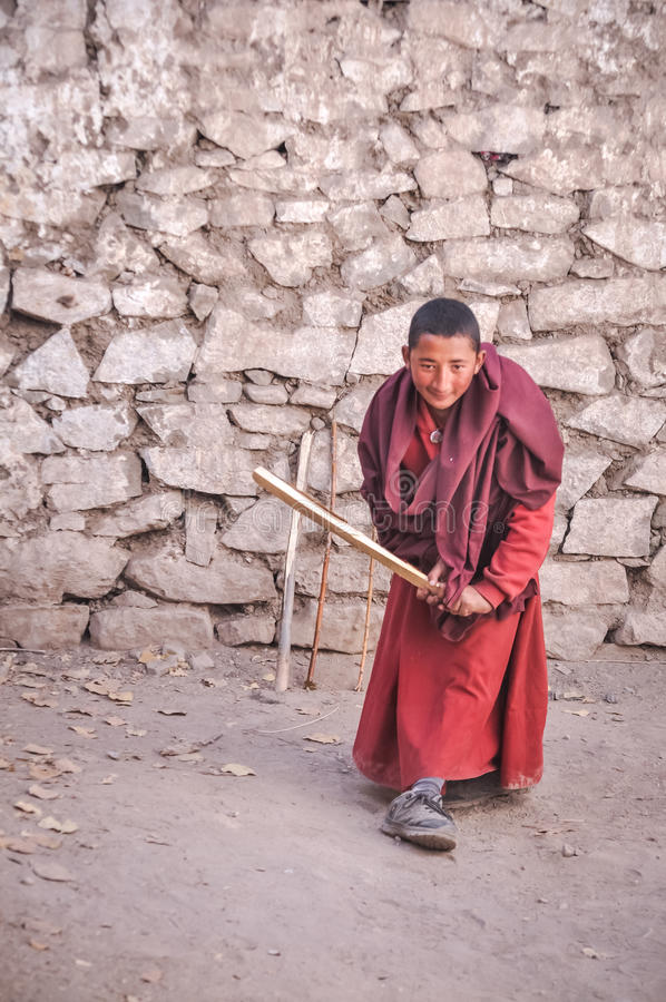 Monk with cricket bat in Ladakh. Hemis, Ladakh - circa November 2011: Young monk dressed in red clothes holds self-made wooden cricket bat and plays cricket at royalty free stock photography