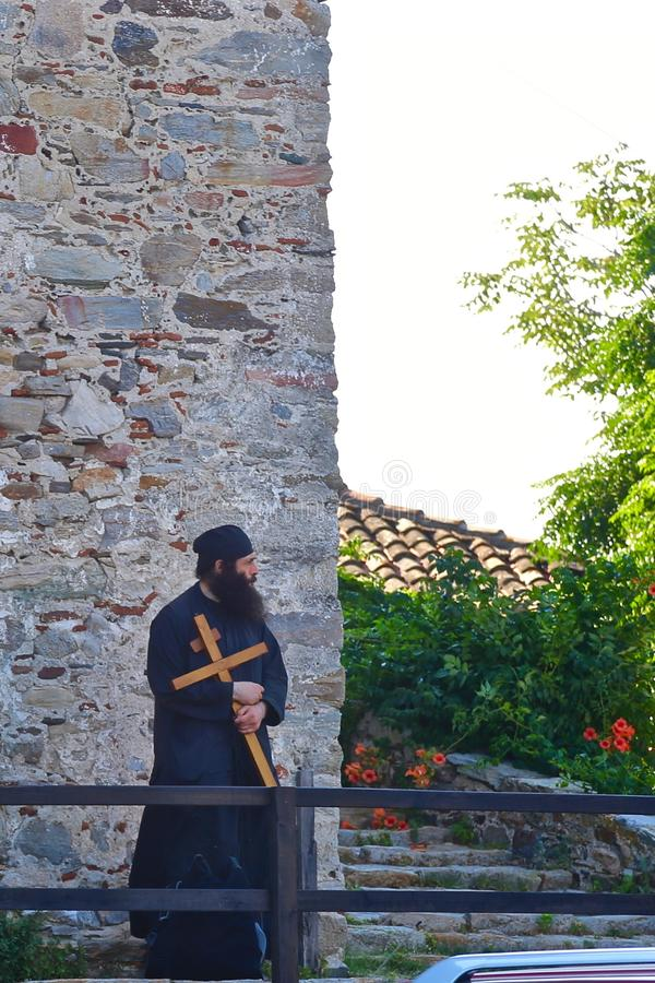 Monk with a cross in his hands royalty free stock photography