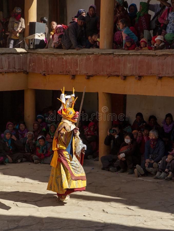 Monk in deer mask with ritual sword performs religious mystery dance of Tantric Tibetan Buddhism on the Cham Dance Festival in Kor royalty free stock images