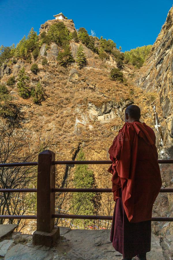 Monk looking out from the Tiger`s Nest Monastery, Bhutan stock photography