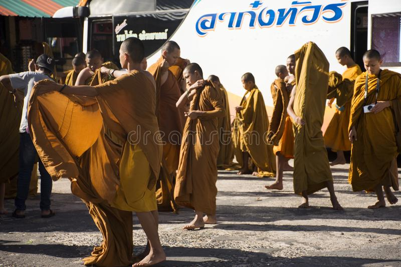 Monk and novice dressed up garments of a Buddhist monk on parking car. Monk and novice dressed up garments of a Buddhist monk on parking before visit and praying stock photo