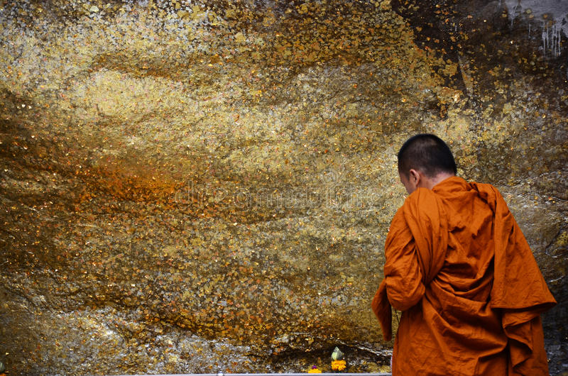 Monk respect praying and gild cover with gold leaf at Lord Buddha image appearing on a cave wall royalty free stock photo
