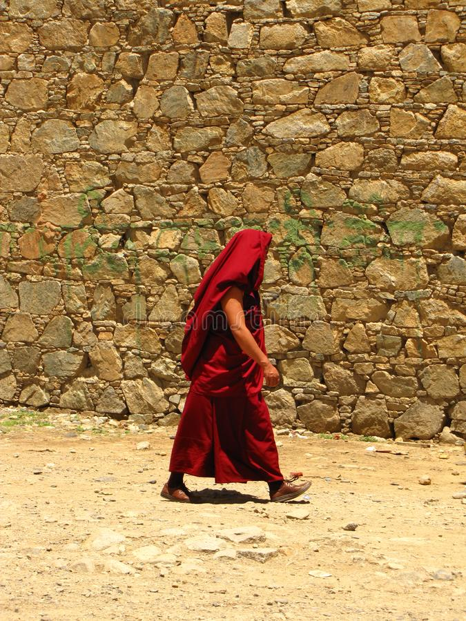 Monk at Samye monastery, Tibet, China. Monk in red clothes walking next to a wall, covering his head as a protection for the sun, at Samye monastery, Tibet stock image
