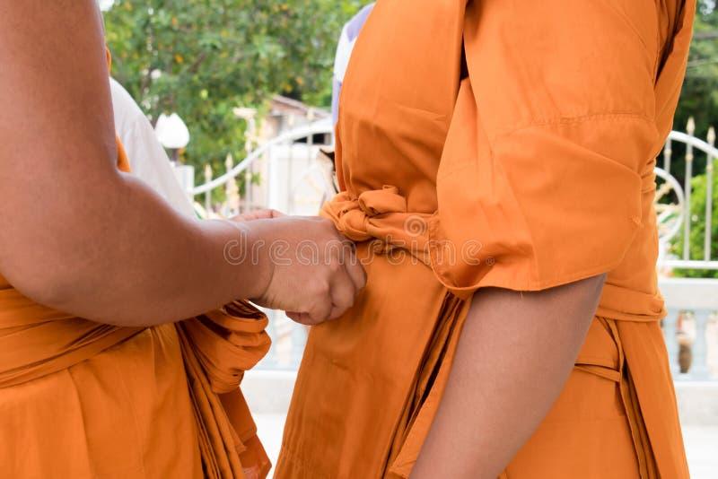 Monk sta coprendo il tessuto Tailandia fotografia stock