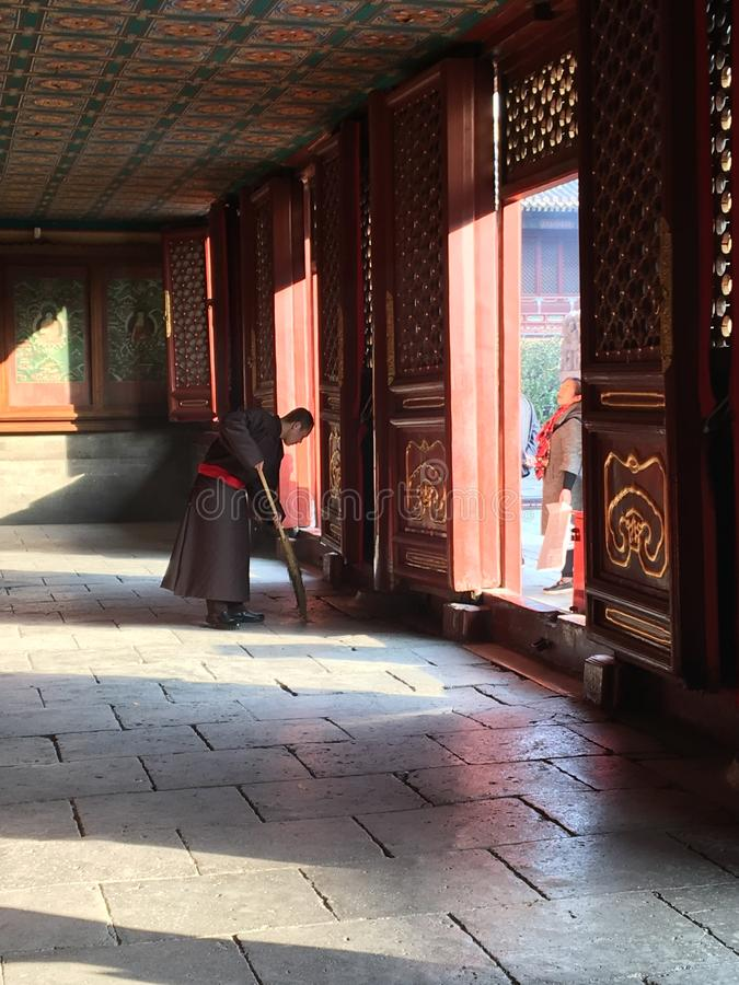 A Monk sweeps the floor in the Lama Temple, Beijing, China. The monk is sweeping the floor at one of the temples of Lama temple area stock photography