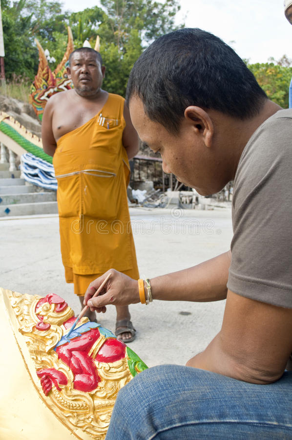 Monk and Temple. A Monk is supervising an volunteer worker painting a Temple Sculpture.The Monk itself is in the background where volunteer worker and his work stock photography