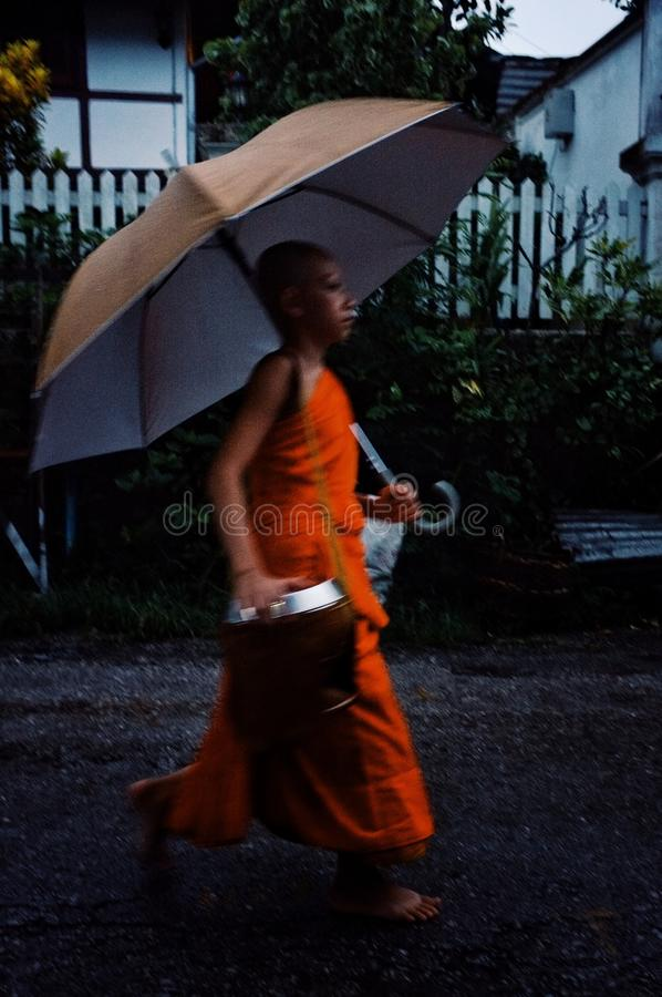 Monk during their early morning round around the town to collect their alms with umbrella stock photo