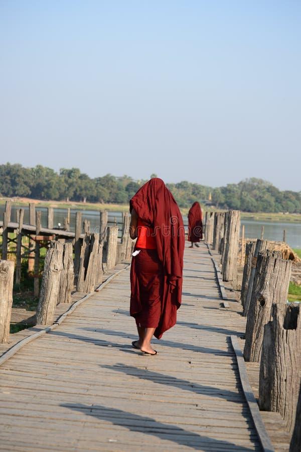 Monk walk along U Bein Bridge royalty free stock photography