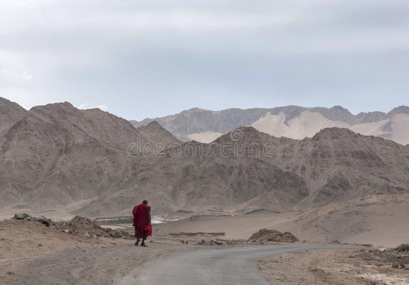 Monk walking with mountain backdrop, Ladakh, India stock photography