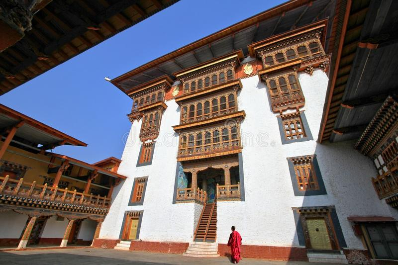 Monk walking in Paro Rinpung Dzong, Buddhist monastery and fortress on a hill near the Paro Chu river. Bhutanese style building d royalty free stock photography