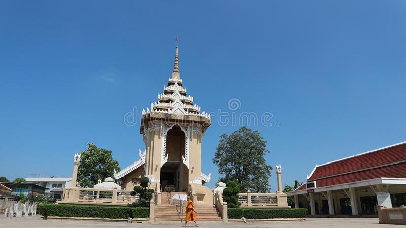 A monk walks in front of a crematorium. PAKKRET, NONTHABURI, THAILAND - OCTOBER 30, 2018: A monk walks in front of a crematorium pavilion at famous temple Wat royalty free stock photography